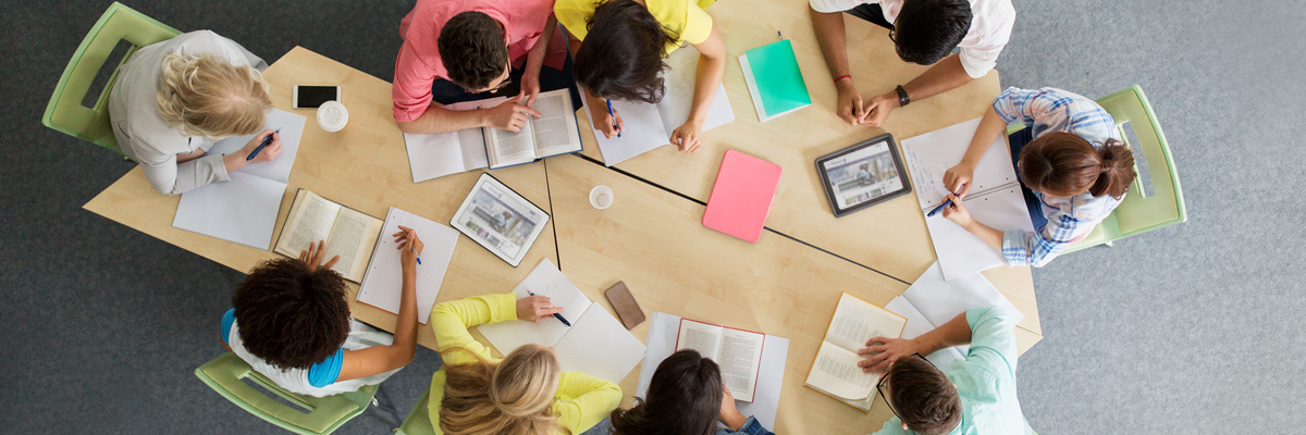 Overhead photo of a group of students at a table with open books and tablets.